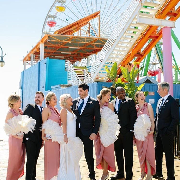 Bride, groom, and wedding party on the Santa Monica Pier