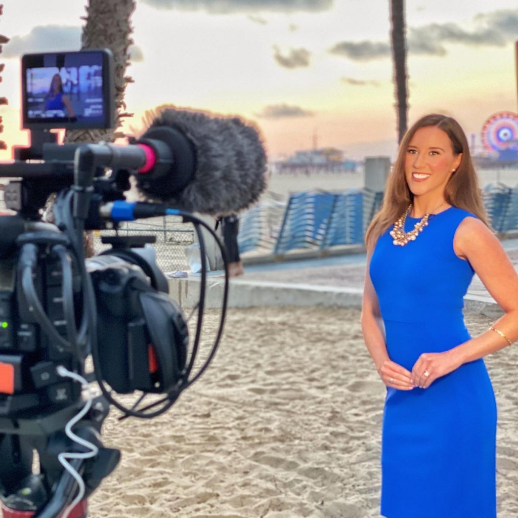 Filming in Santa Monica - Maggie Clark wears a blue dress on the Santa Monica Beach as a camera operator prepares to film her with the Santa Monica Pier | Photo by Magie Clark, @MaggieClarkOnCamera