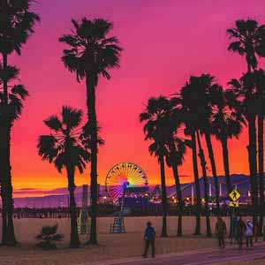 A view of an orange and pink sunset be the Santa Monica Oier | Photo by @thatislandview