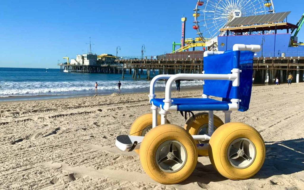 Beach wheelchair on sand in front of the Santa Monica Pier