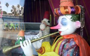 A marionette doll holding a flute