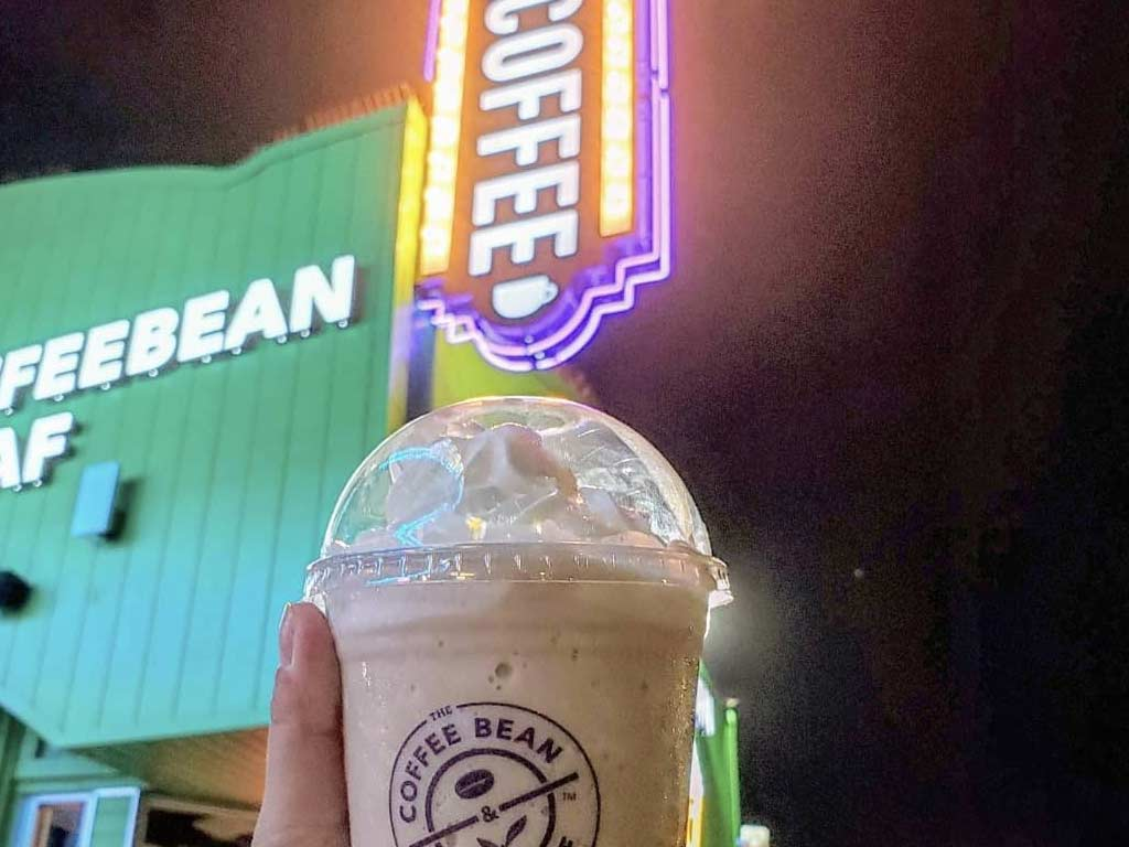 Ice blended drink in front of coffee sign