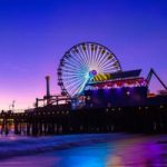A multi-colored Ferris wheel reflects off the water by the Santa Monica Pier   Photo by Scott Trento, Upsplash