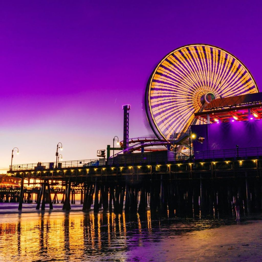 The Ferris wheel in Santa Monica in yellow on a pink and purple sky | Photo by @michaeltsirakis